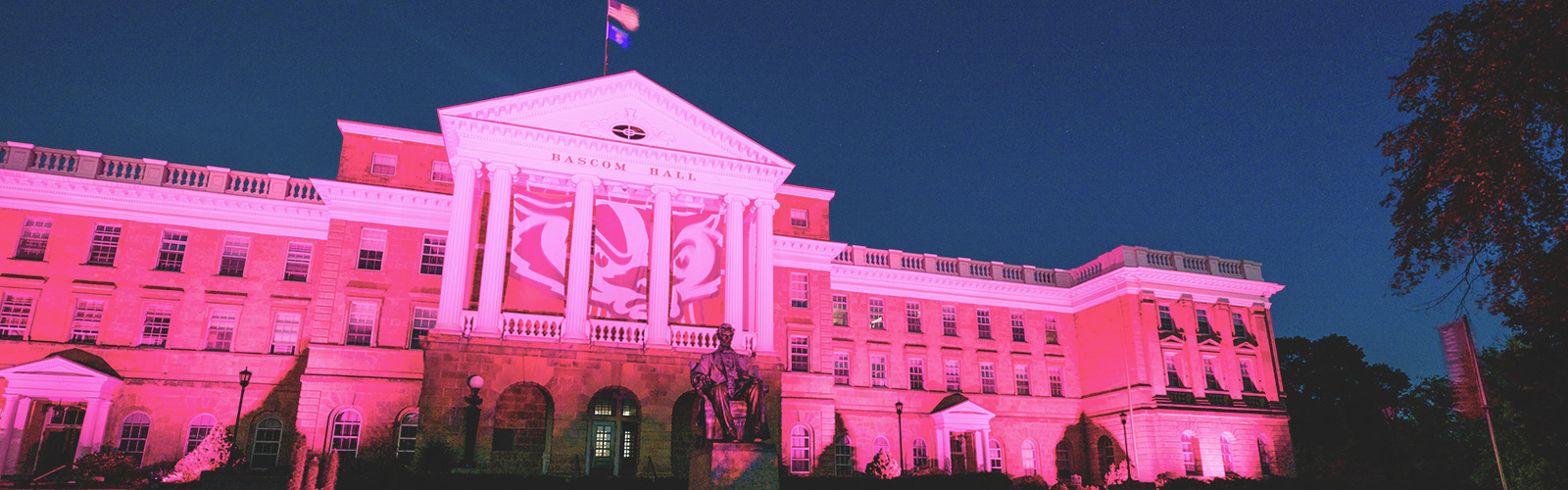 In honor of Breast Cancer Awareness Month, pink accent lighting illuminates the exterior of Bascom Hall and terrace plantings surrounding the Abraham Lincoln statue at the University of Wisconsin-Madison as dawn brightens the night sky on Oct. 20, 2017. Hanging between the building's column is a graphic banner of UW-Madison mascot Bucky Badger. (Photo by Jeff Miller / UW-Madison)